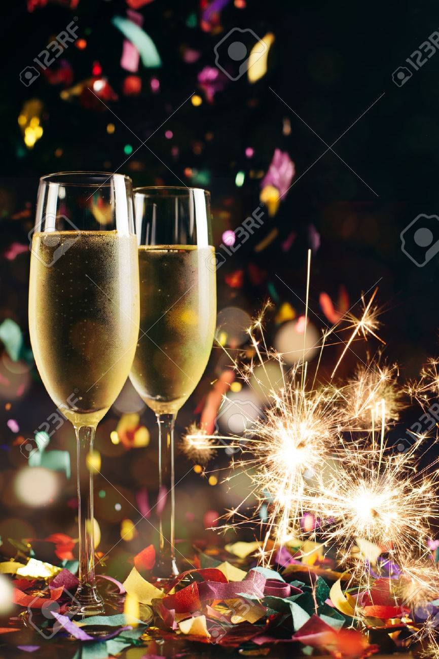 Two bright icy champagne glasses, confetti falling and sparklers - 47071067