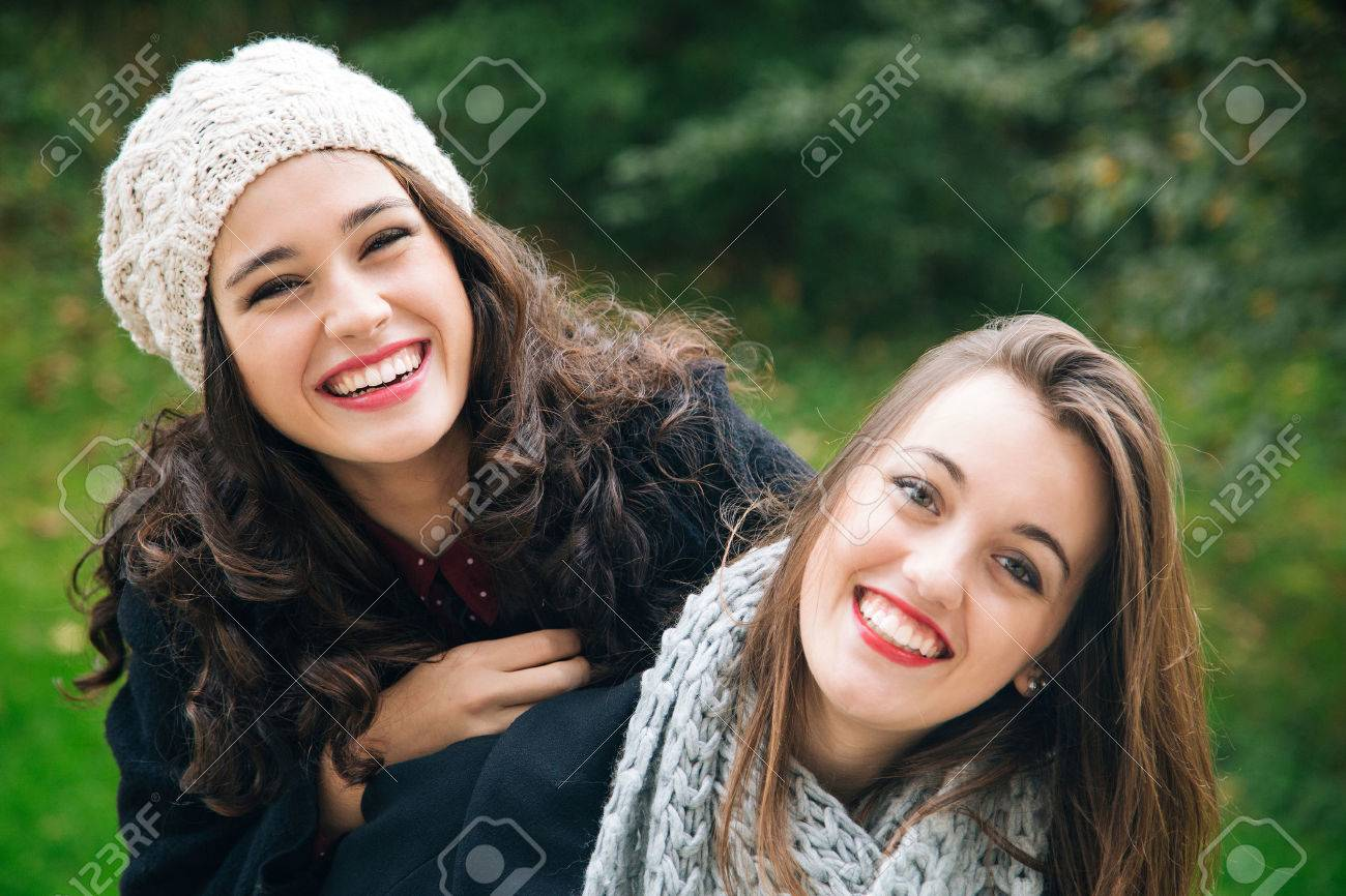 Cute best friend girls a piggyback in winter or fall outdoors - 47210004