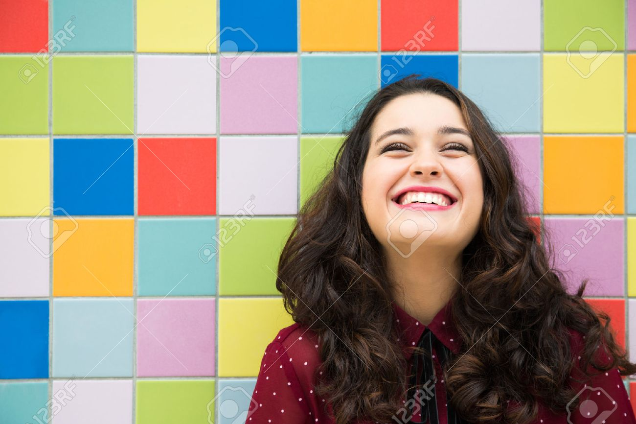 Happy girl laughing against a colorful tiles background. Concept of joy - 47210960