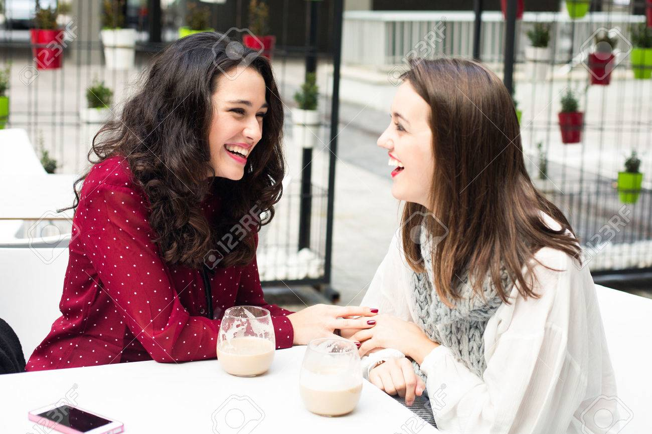 Young cute women laughing while having a coffee outdoors - 47724639
