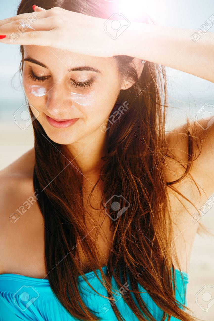 Young beautiful woman in bikini with sun cream in cheeks protecting from the sun with hand as a sun visor in the beach. Skin and hair protection concept. - 50835031