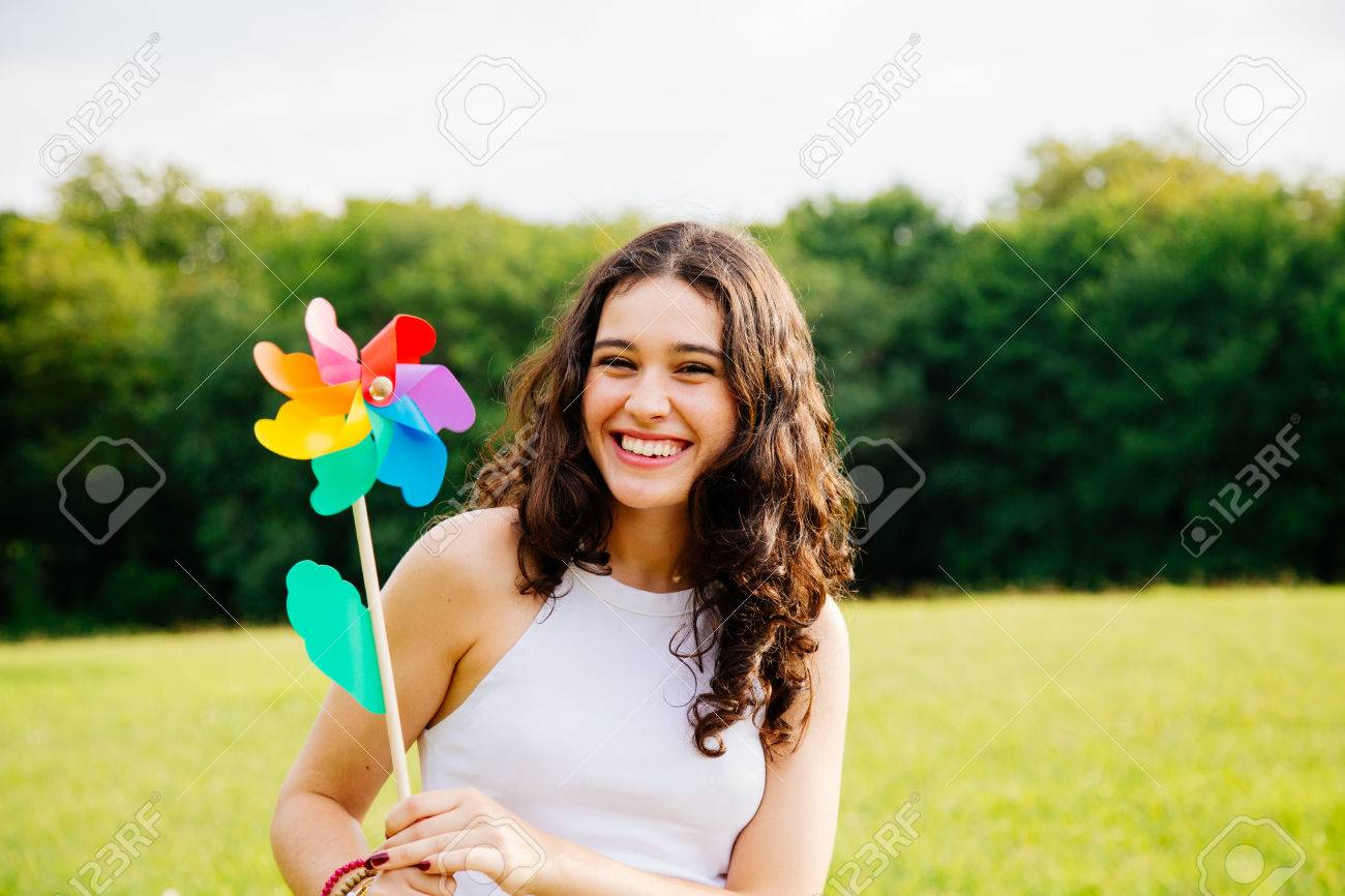 Cheerful and beautiful young woman holding a windmill toy in a green landscape - 70258564