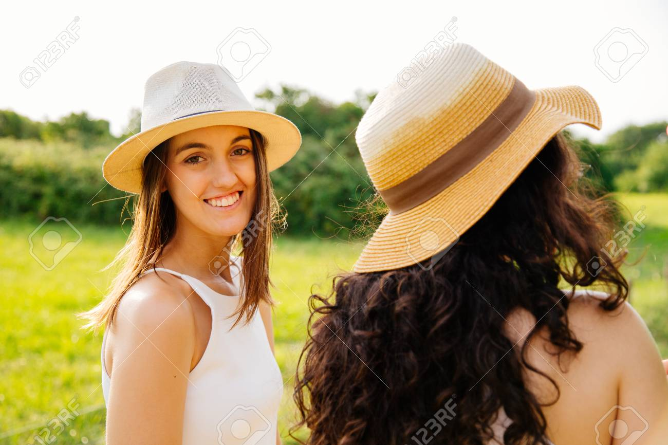 Happy young women with hats walking on the fields in summer turning to  camera Stock Photo 3a4c610a995