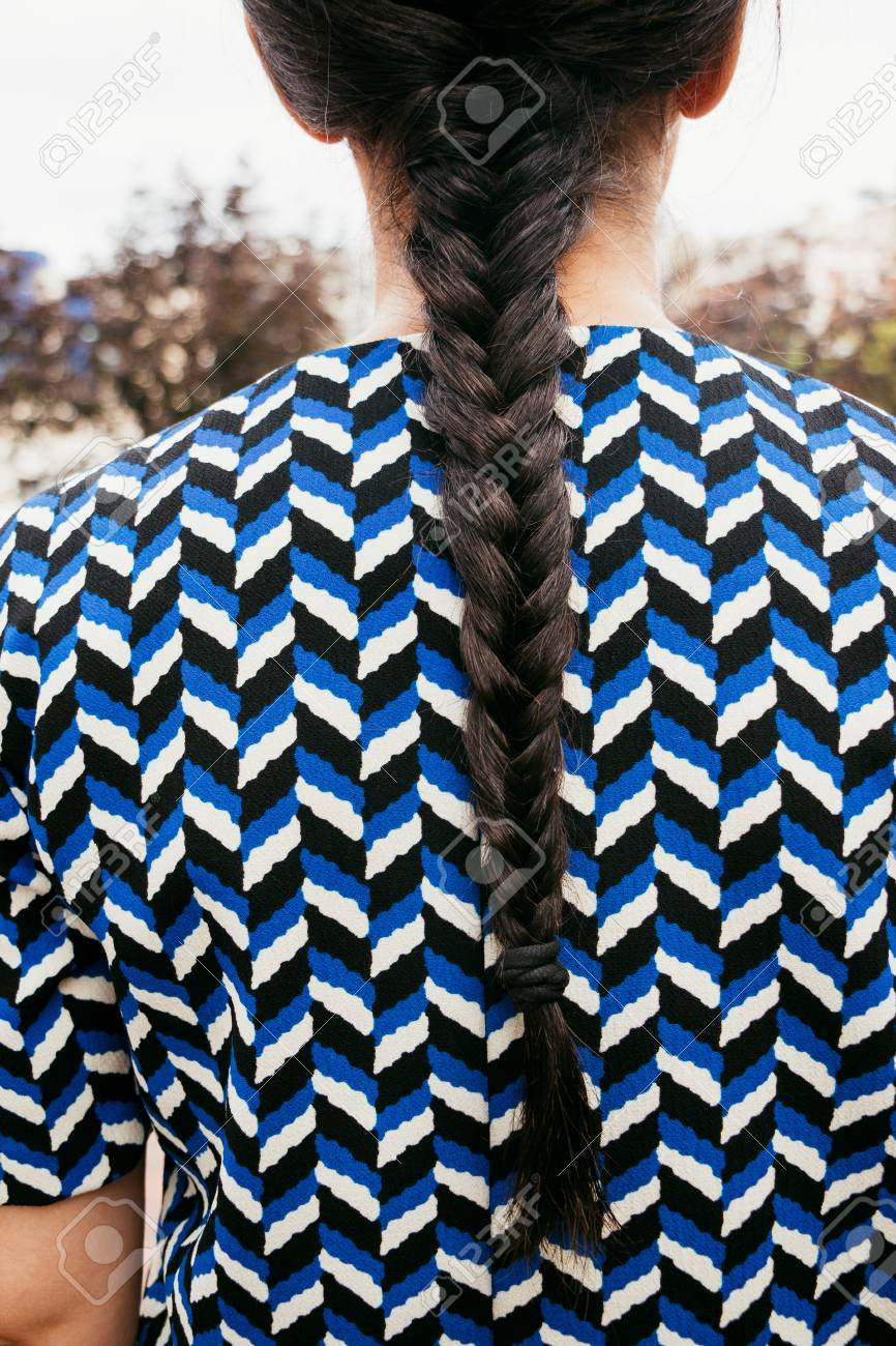 72ba3d2a6914e Stock Photo - Young woman with braid and herringbone pattern dress in the  street. Back view.