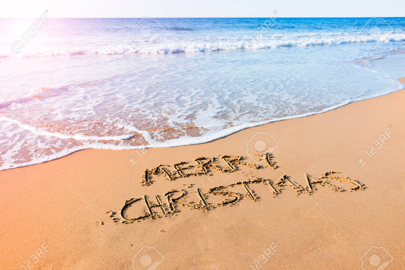 Christmas Beach.Merry Christmas Written In The Sand At The Seashore On The Beach
