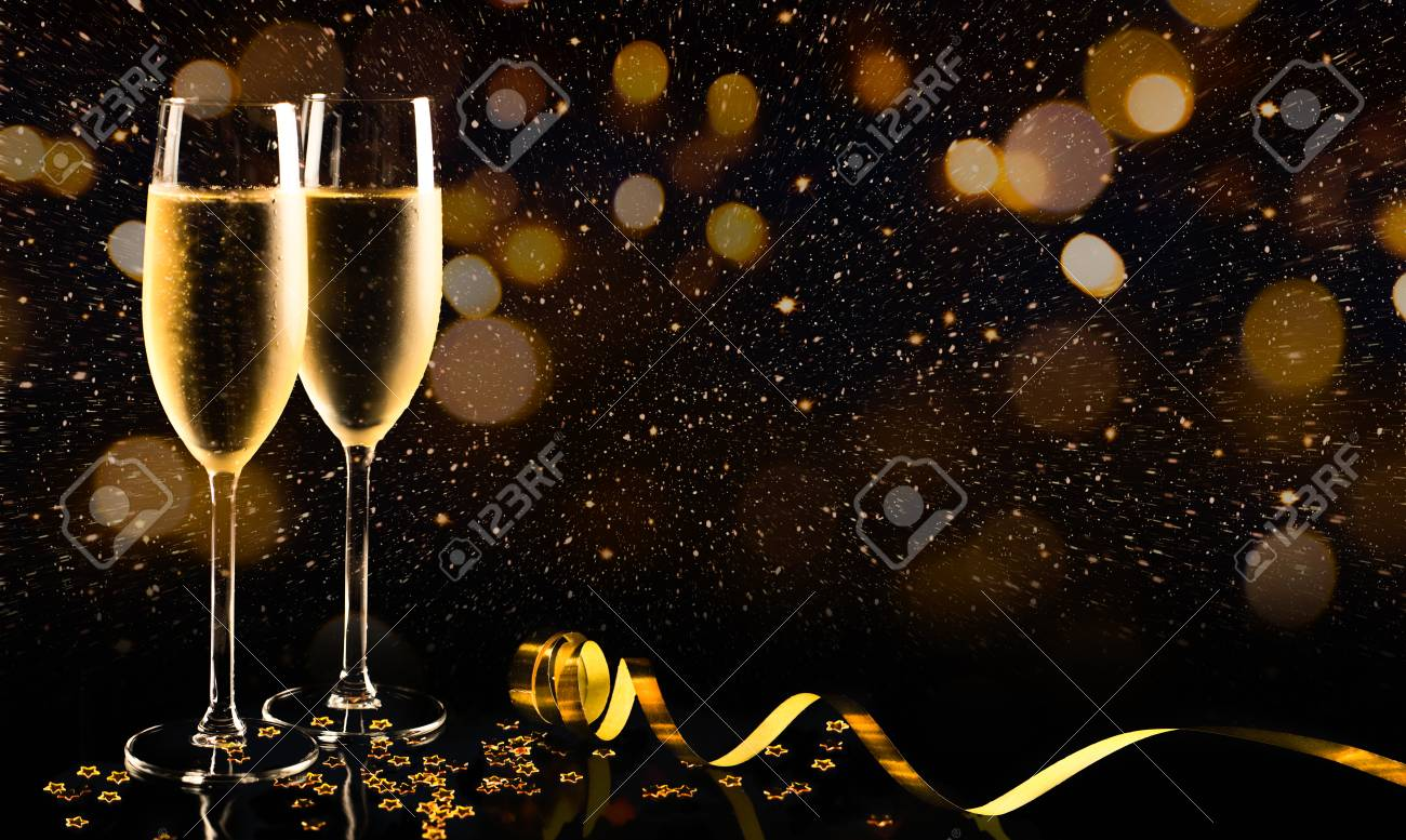 Two glasses of champagne with golden confetti, glitter, serpentine and lights. Night of celebration concept - 87021077