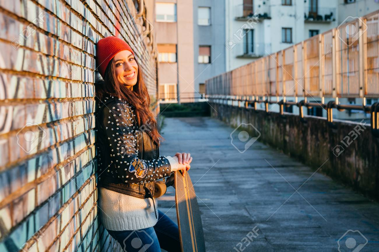 Young and beautiful skater woman enjoying the sunset in the city resting on a brick wall with graffiti - 91116038