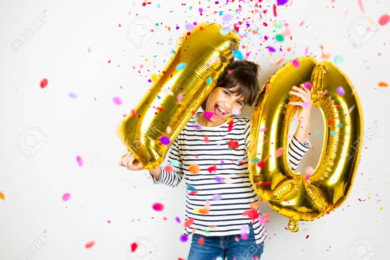 Happy little girl holding two golden balloons making the 10 number while falling confetti on white background. 10th anniversary celebration party. - 91614578