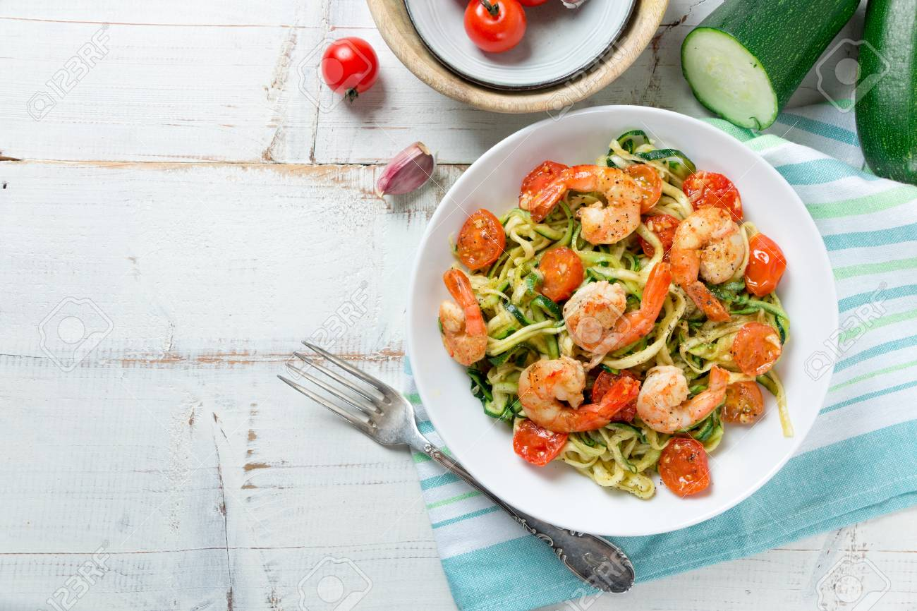 Zucchini noodles sauteed with tomato cherry and prawns in a dish on a rustic white wooden table. Top view - 94224186