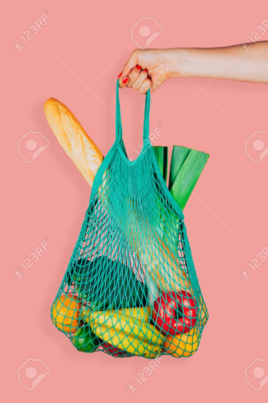 Woman hand holding a green mint string shopping bag with vegetables, fruits and bread in front of a pink background - 102747561