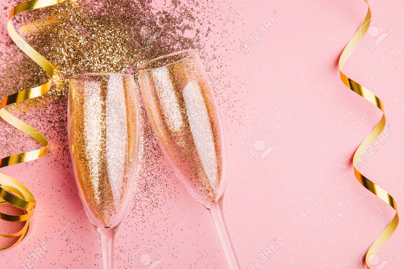 Two glasses of champagne toasting with golden confetti, glitter and serpentine on a pink background. Flat lay. Night of celebration concept - 109282271