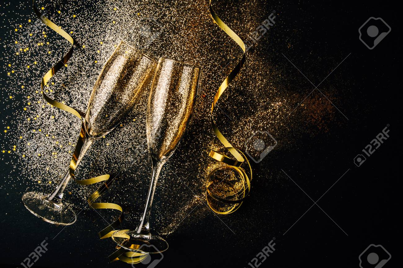Two glasses of champagne toasting with golden confetti, glitter and serpentine on a dark background. Flat lay. Night of celebration concept - 108473680