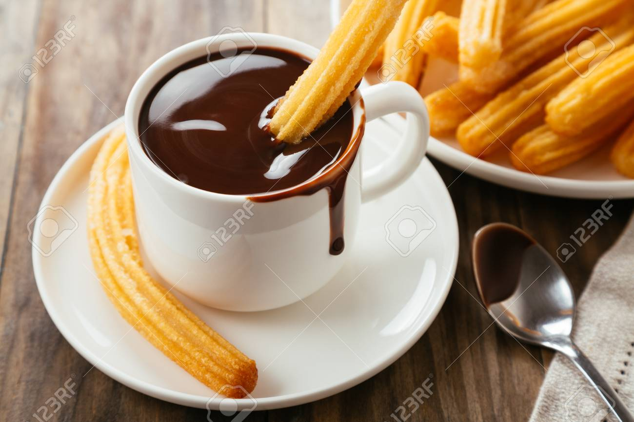 Traditional spanish churros with hot chocolate sauce on a rustic wooden table - 112463478