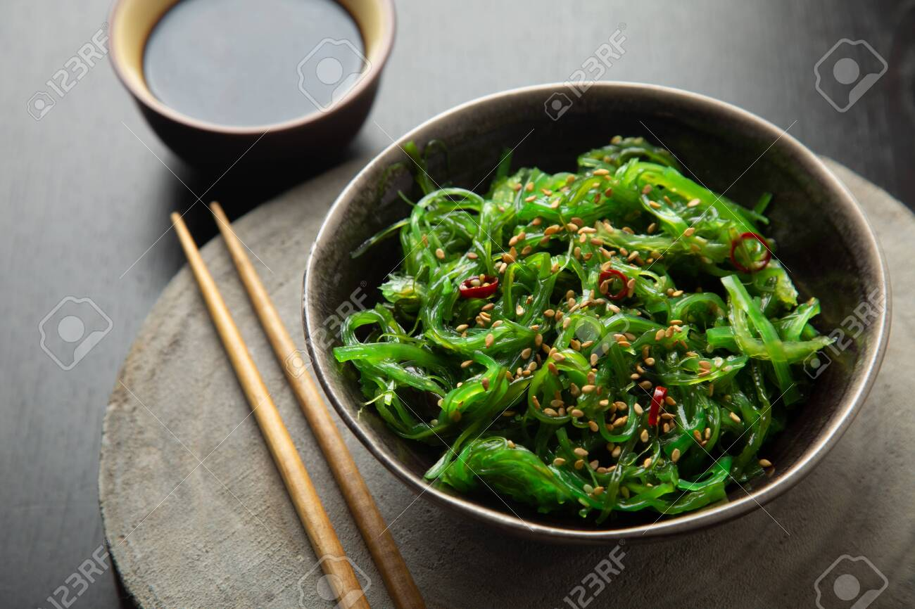 Wakame seaweed salad with sesame seeds and chili pepper in a bowl on a wooden slice - 122301234