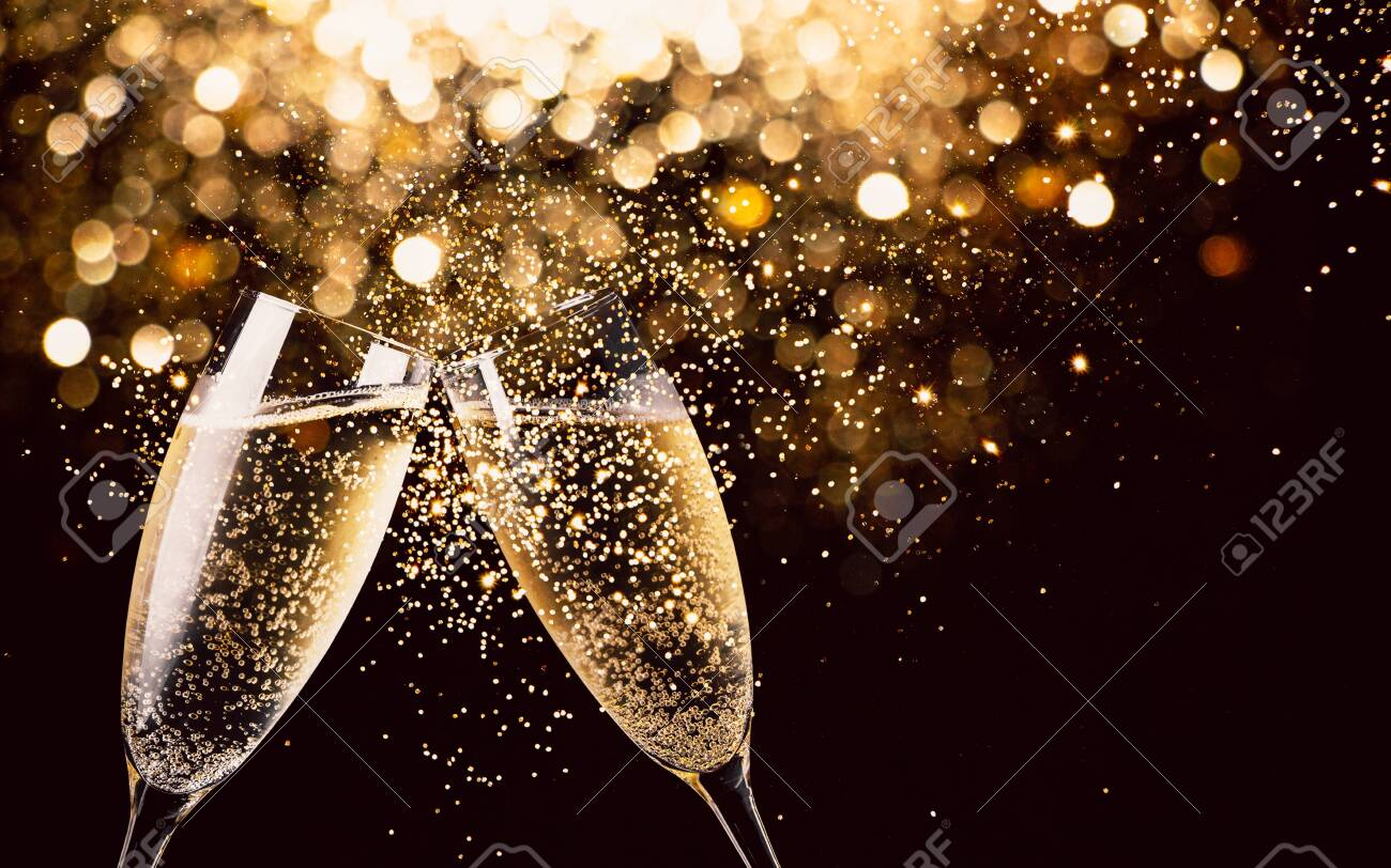 Two glasses of champagne toasting in the nigh with lights bokeh, glitter and sparks on the background - 131608629