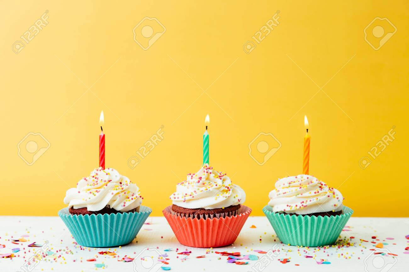 Three colorful birthday cupcakes with candles and confetti on a yellow background - 145836201