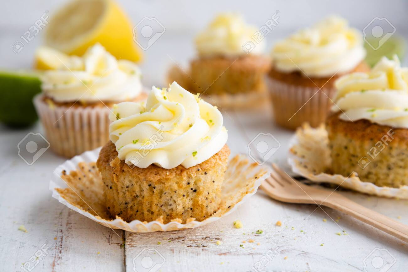 Lemon and poppy seed cupcakes with cheese cream frosting and lemon and lime zest on a rustic white wooden table - 147722526