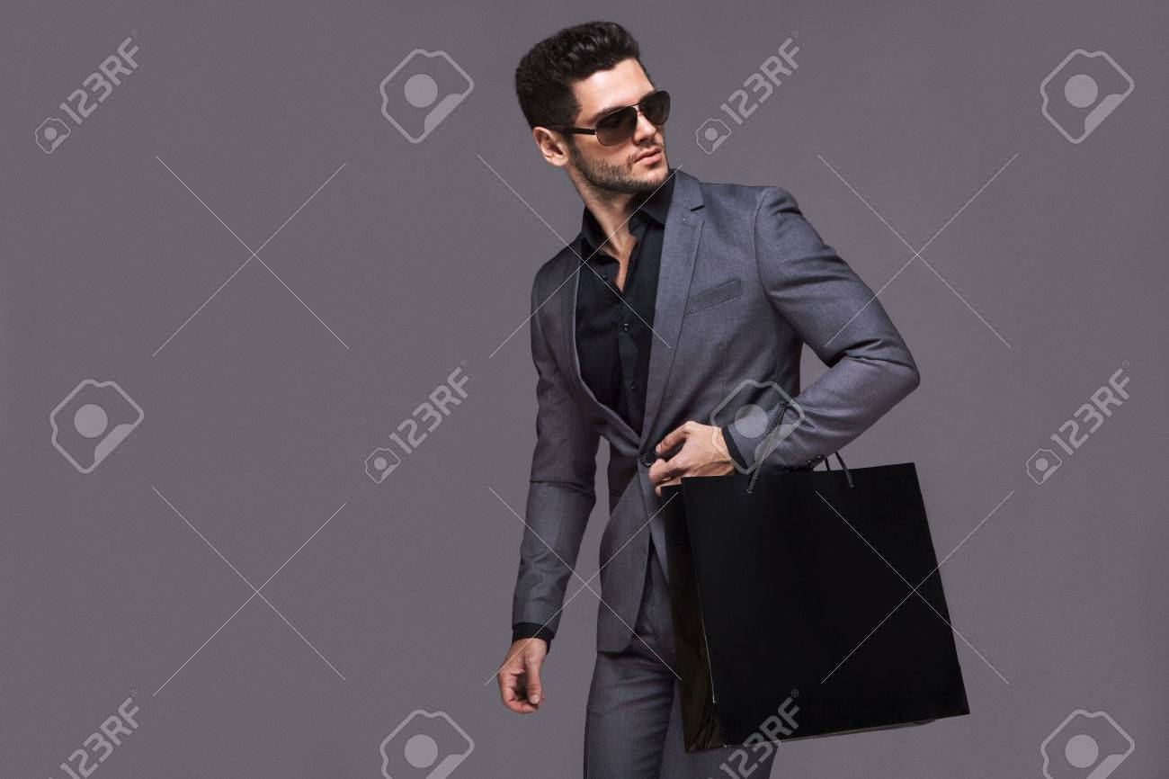Handsome man in suit with shopping bag - 50580025