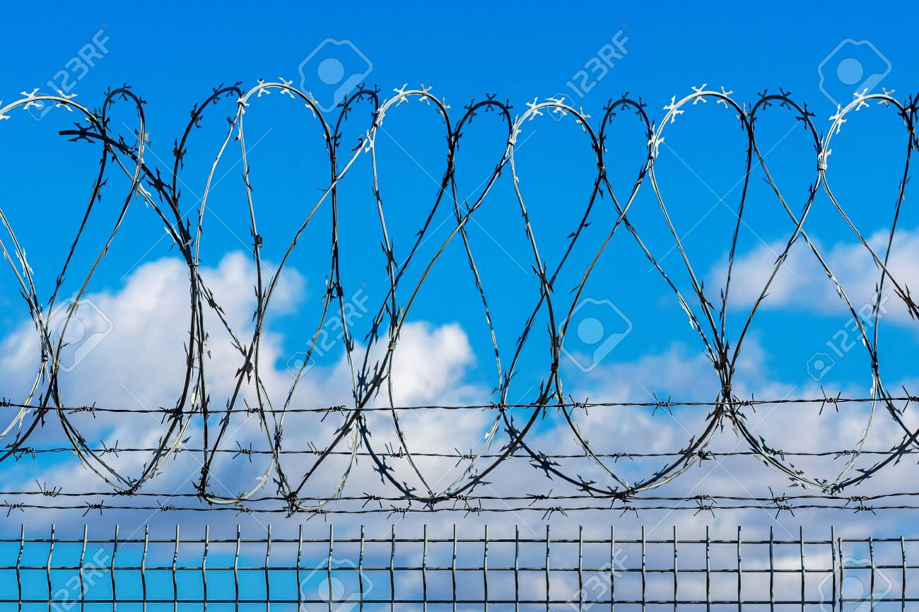 fence with barbed wire against blue sky with clouds, security concept - 144062836