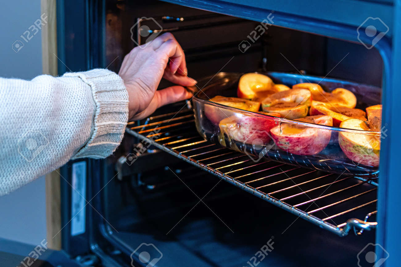 glass container with sliced stuffed apples in the oven, close-up, homemade dessert concept - 157565354