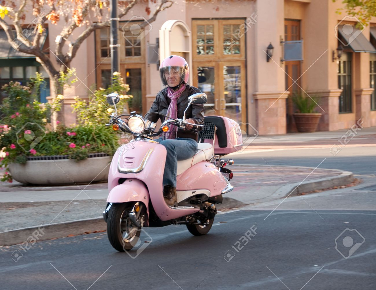 a sixty year old woman on her pink motorbike - 5944334