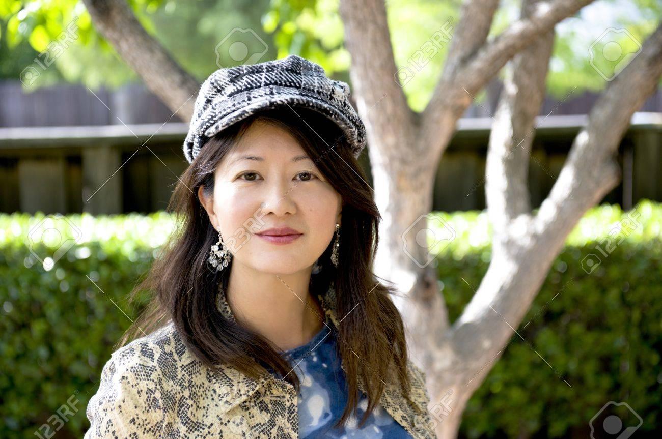 smiling asian woman with herringbone cap - 13941665