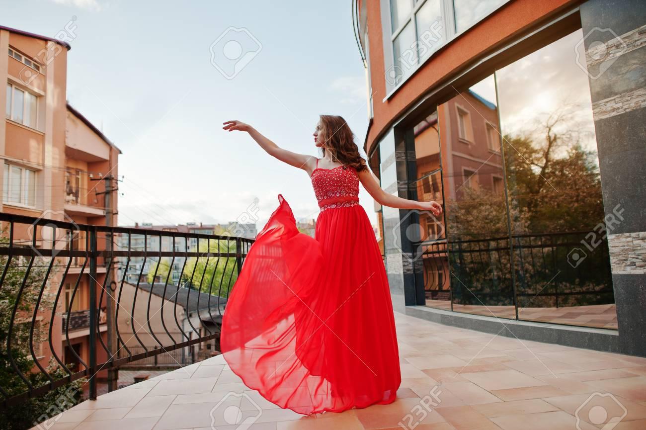 El Retrato De La Muchacha De Moda En El Vestido De Noche Rojo Presentó La Ventana Del Espejo Del Fondo Del Edificio Moderno En El Balcón De La