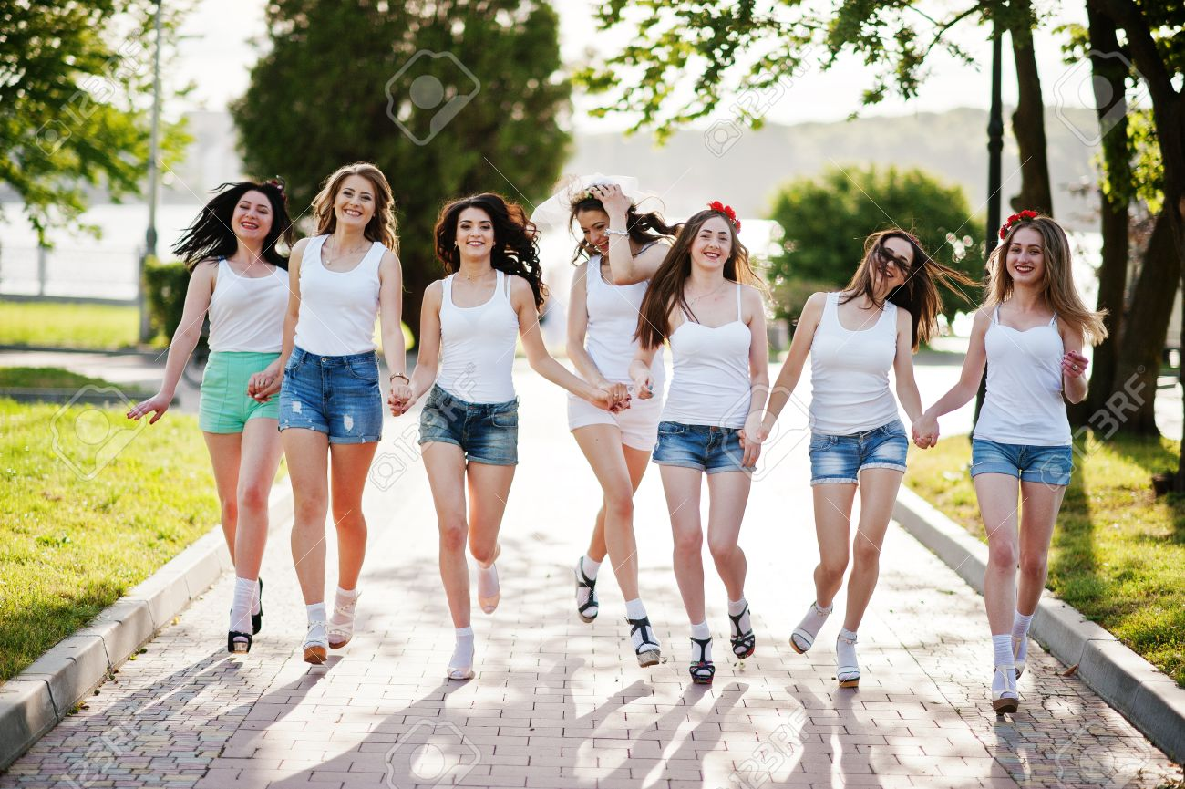 3d56e81df8ea Seven happy and sexy girls on short shorts and white shirts running fun on  road at
