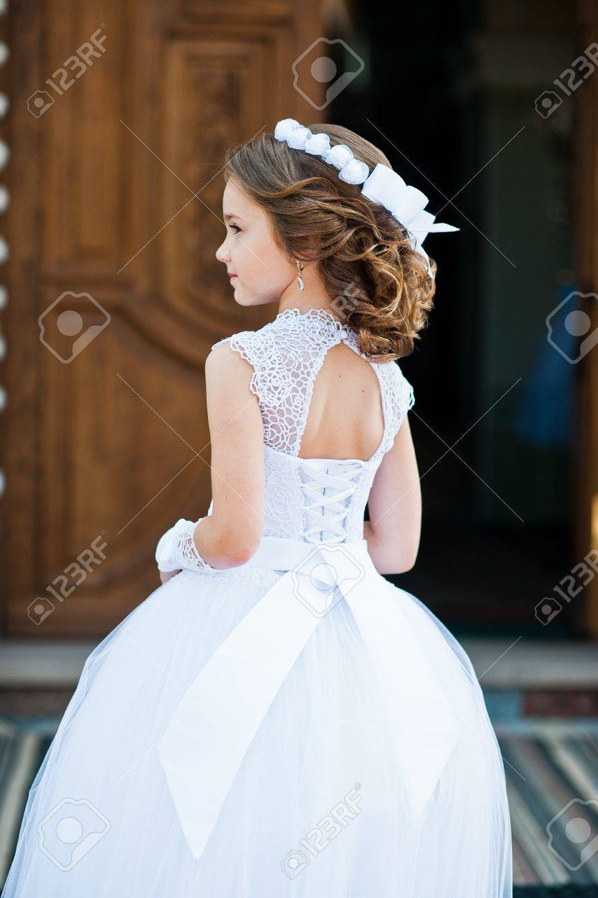 Portrait Of Cute Little Girl On White Dress And Wreath On First