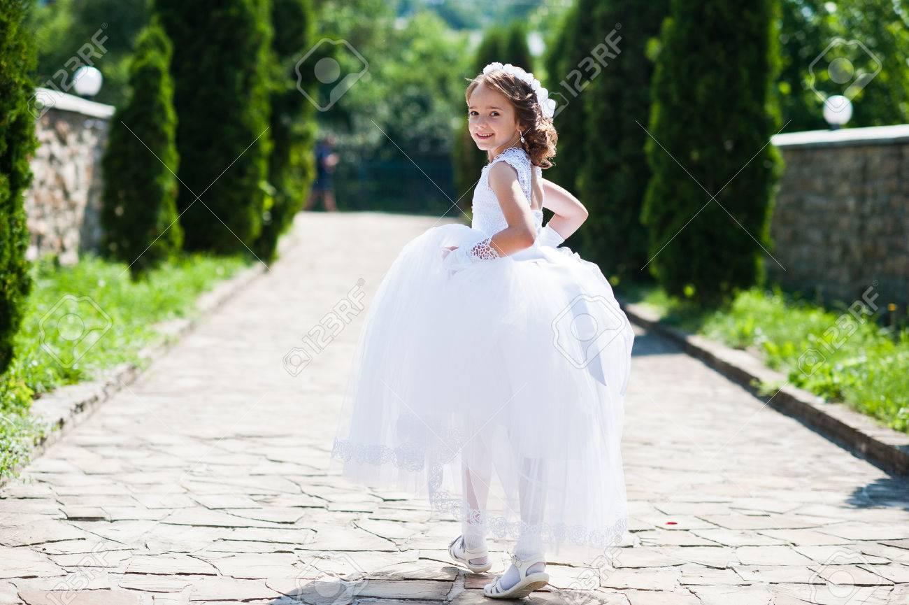 design de qualité c43a3 0f970 Portrait de petite fille mignonne sur la robe blanche et couronne de  première sainte communion fond thuya allée