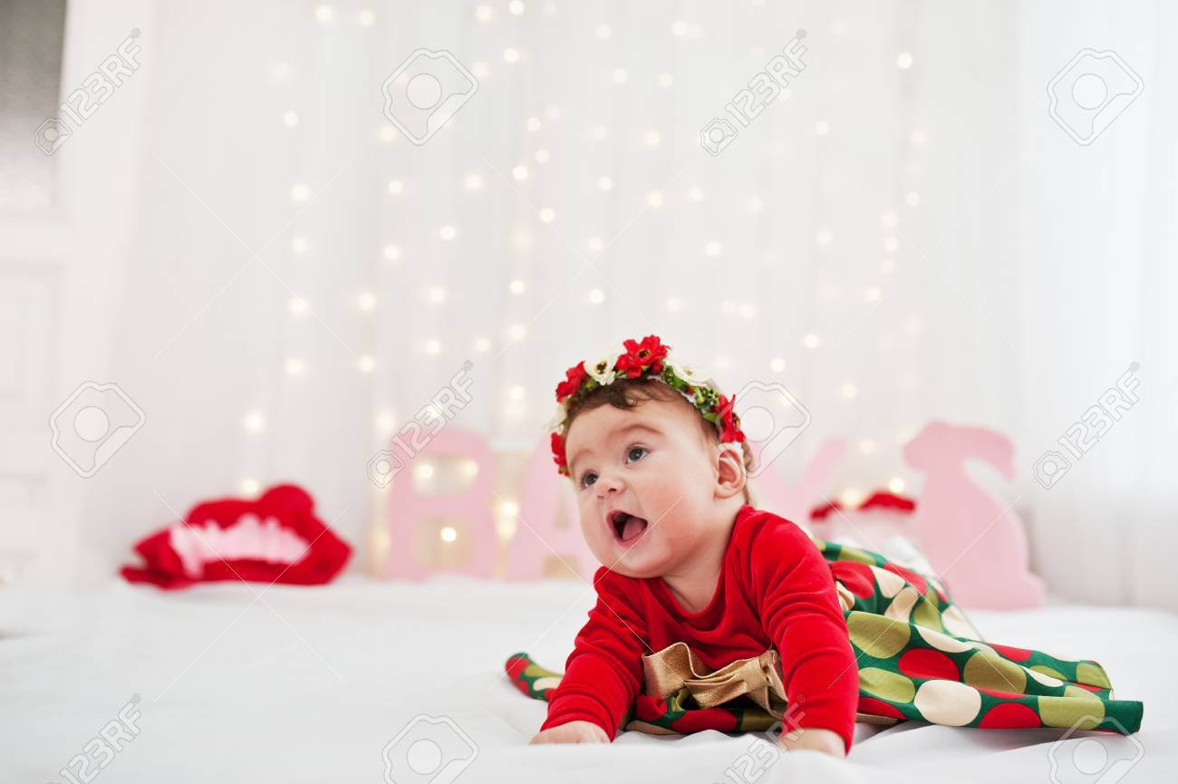 bc7f08b6a196f Cute little baby girl with wreath and on red dress posed on the bed Stock  Photo