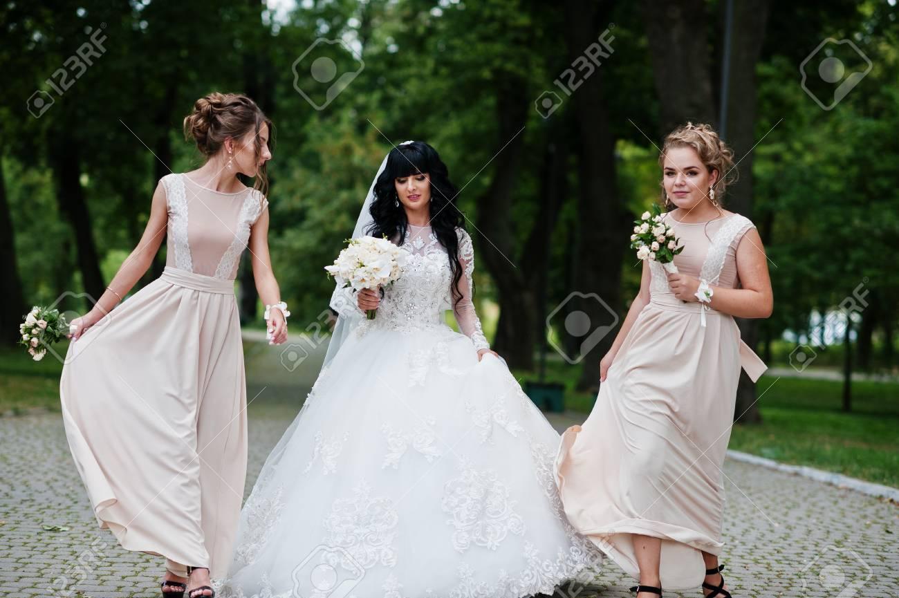 Feine Braut Mit Brautjungfern In Beige Kleid Auf Weg Auf Park Mit ...