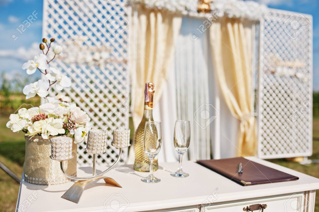 Table of newlyweds with champagne glasses and candlestick background wedding arch. - 66152453