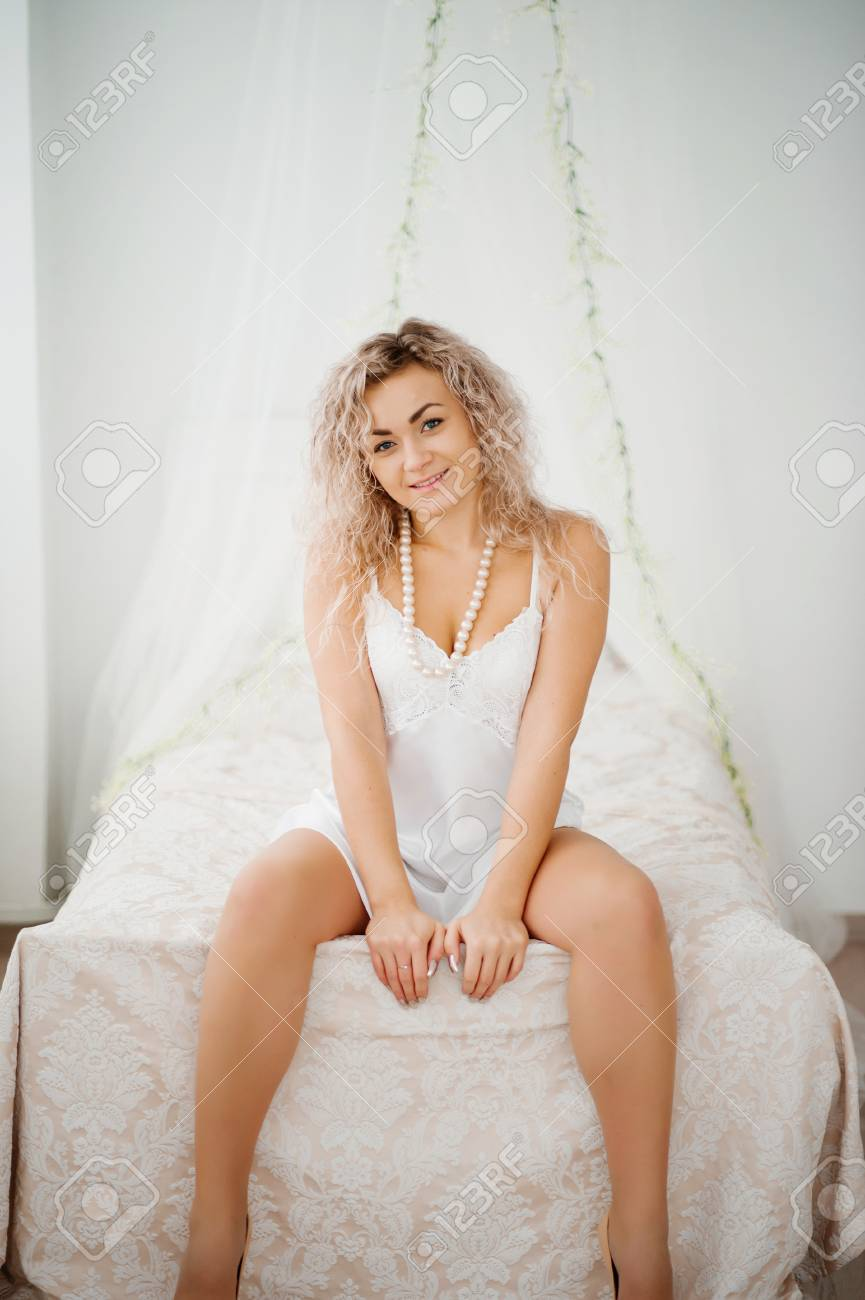bed57801e4b Сurly blonde girl in a white silk gown boudoir robe on bed.