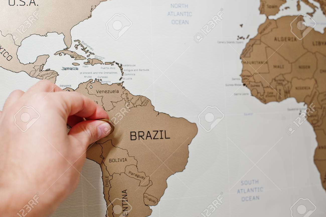 Scratch travel map of the world. Hand of man erase zil with.. on