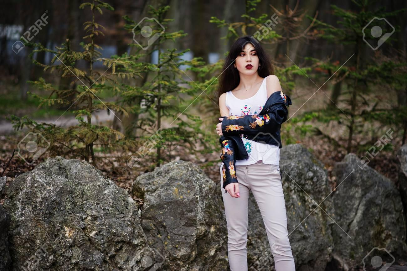 La ragazza zingara del Brunette ha proposto contro le pietre sulla sosta. Abbigliamento da modella su giacca di pelle e t shirt con ornamento,