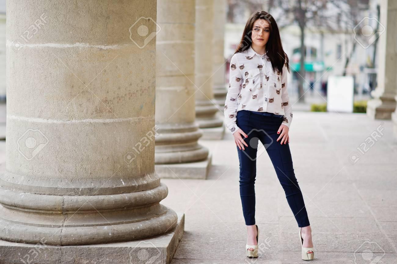 3cdaac6f57bce Banque d'images - Jeune fille brune élégante sur la chemise, le pantalon et  les chaussures à talons hauts, posés près des colonnes de pierre.