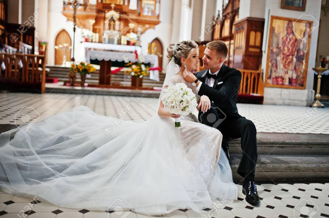 Photosession du couple de mariage élégant sur l\u0027église catholique.