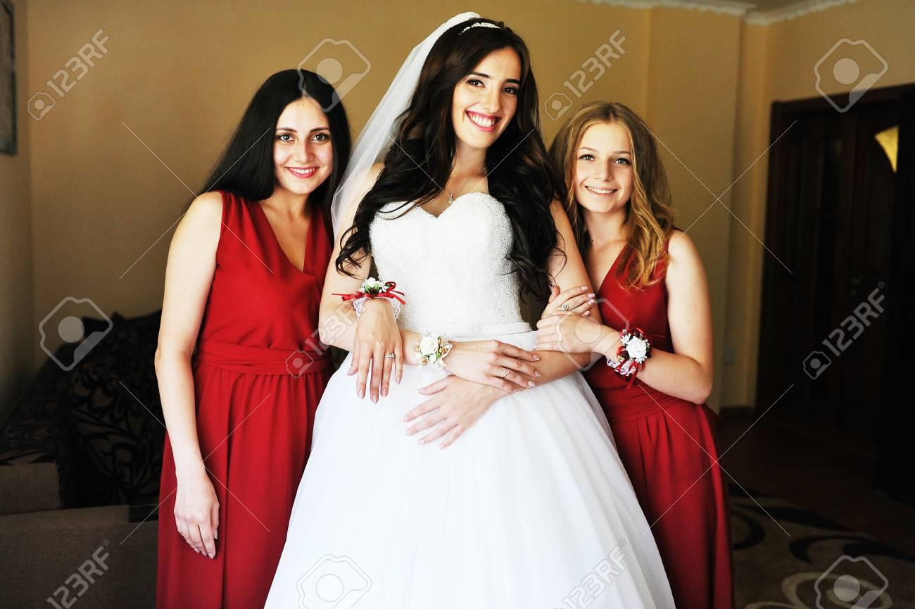 check out 7ec2d 8197b Felice bruna bruna sposa indossa la sua camera con due damigelle d'onore su  abito rosso.