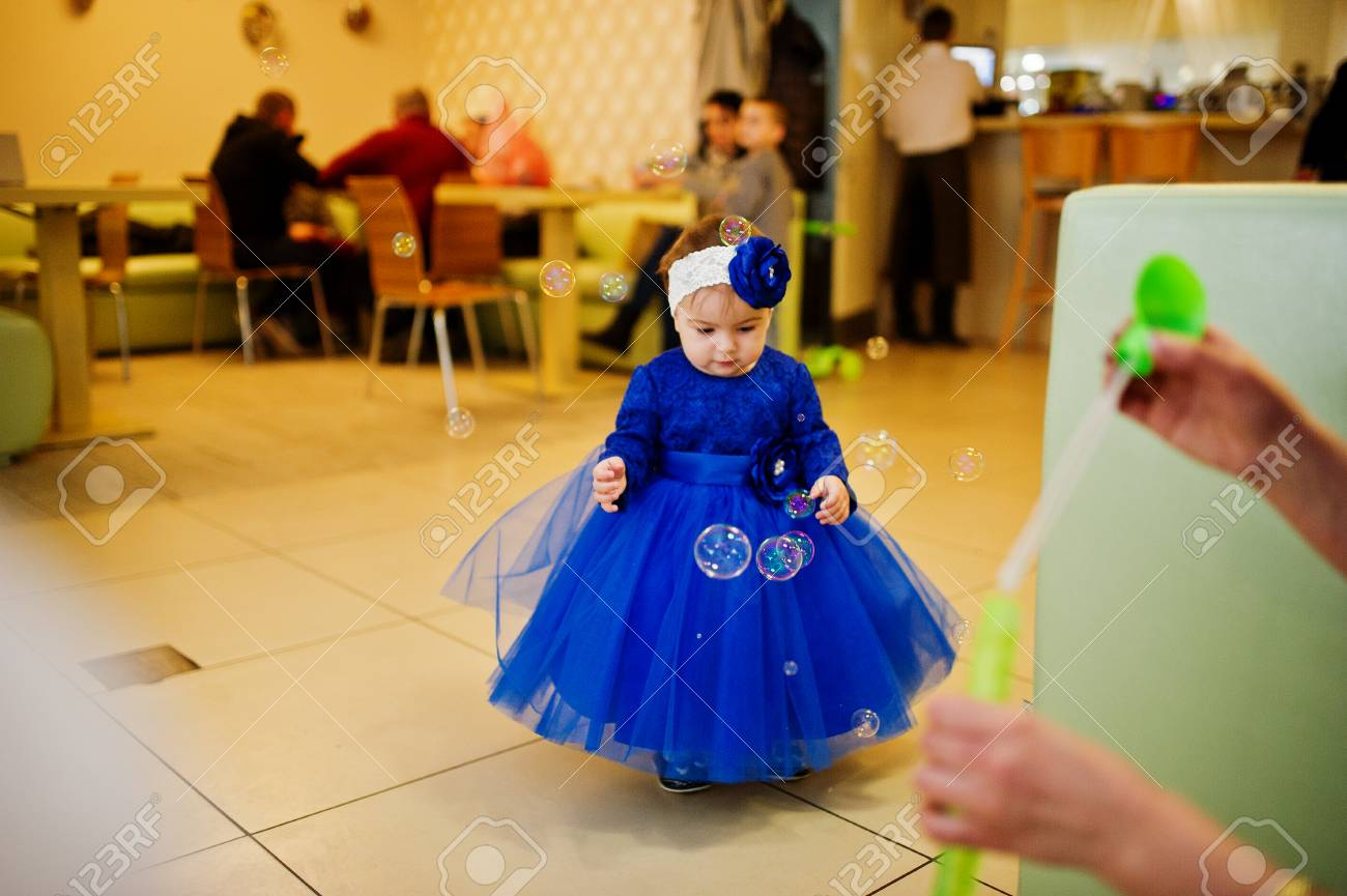 c0a277803 Cute Little Baby Girl At Blue Dress Play With Soap Bubbles. 1 ...