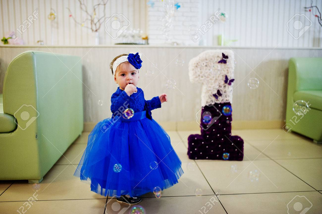 ea9e4747d Cute little baby girl at blue dress play with soap bubbles. 1 year birthday  day