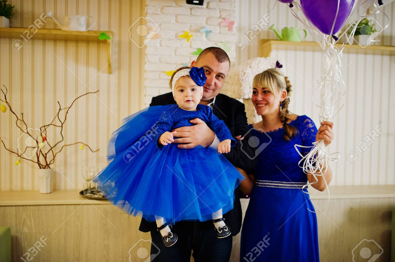 d34ae3d57 Cute little baby girl at blue dress on hands of father and mother...