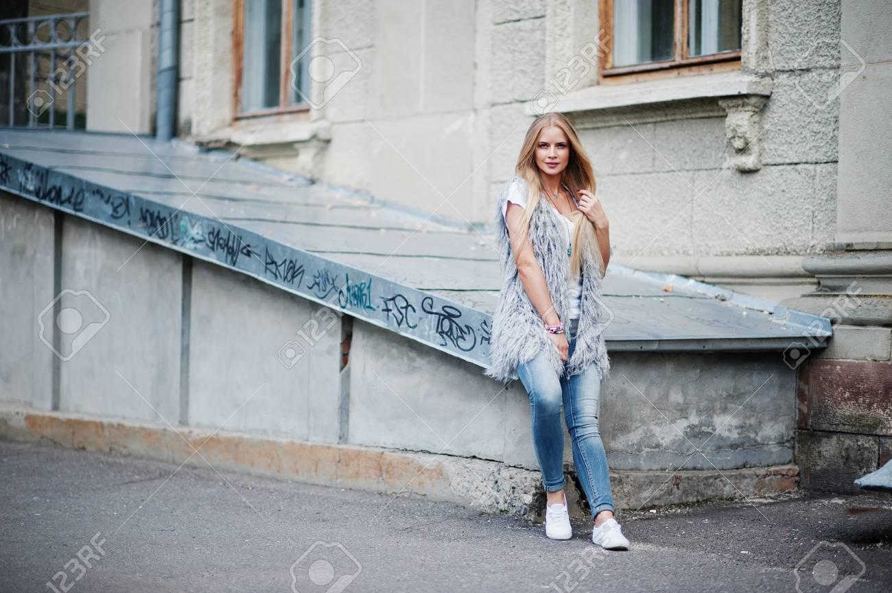 d1436dae0 Elegante mujer rubia vestida en jeans y chica sin mangas con camisa blanca  contra la cámara