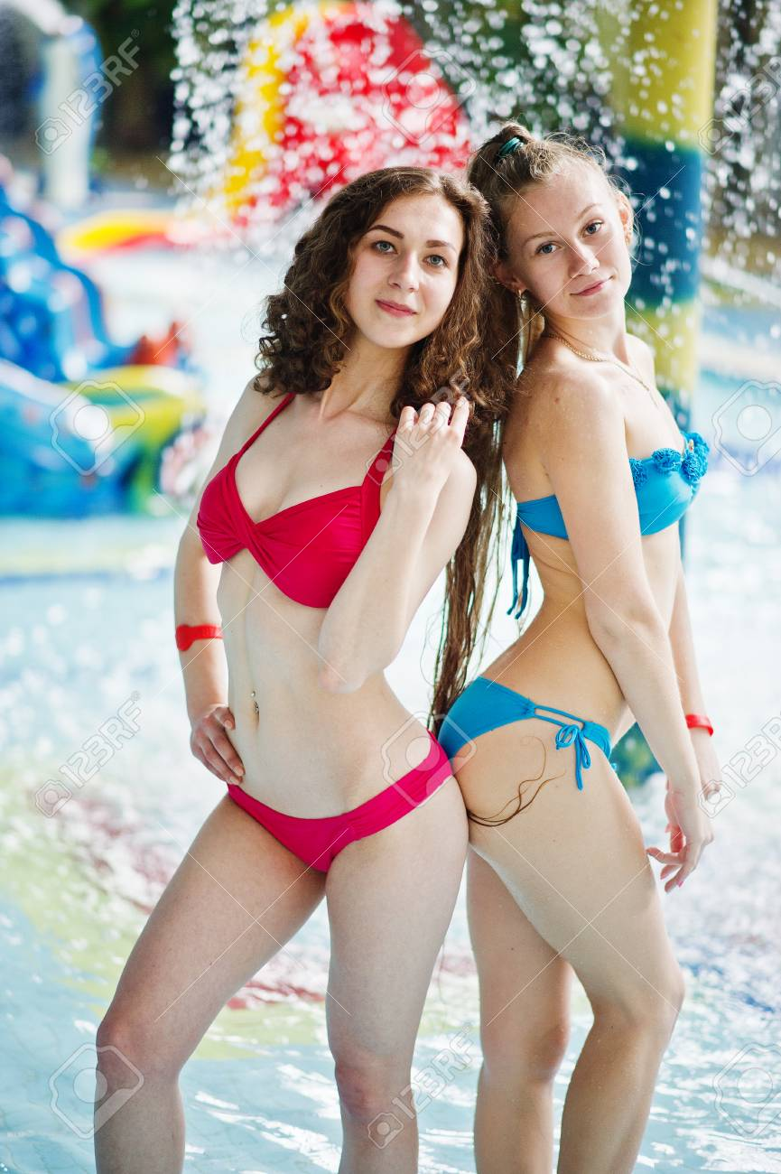 Stock Photo - Two fantastic girls posing in the pool in the water park  wearing red and blue swimsuit.