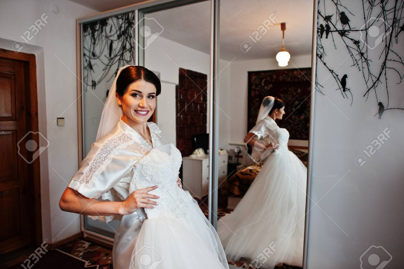 Fabulous Bride Holding Her Sophisticated White Wedding Dress Stock