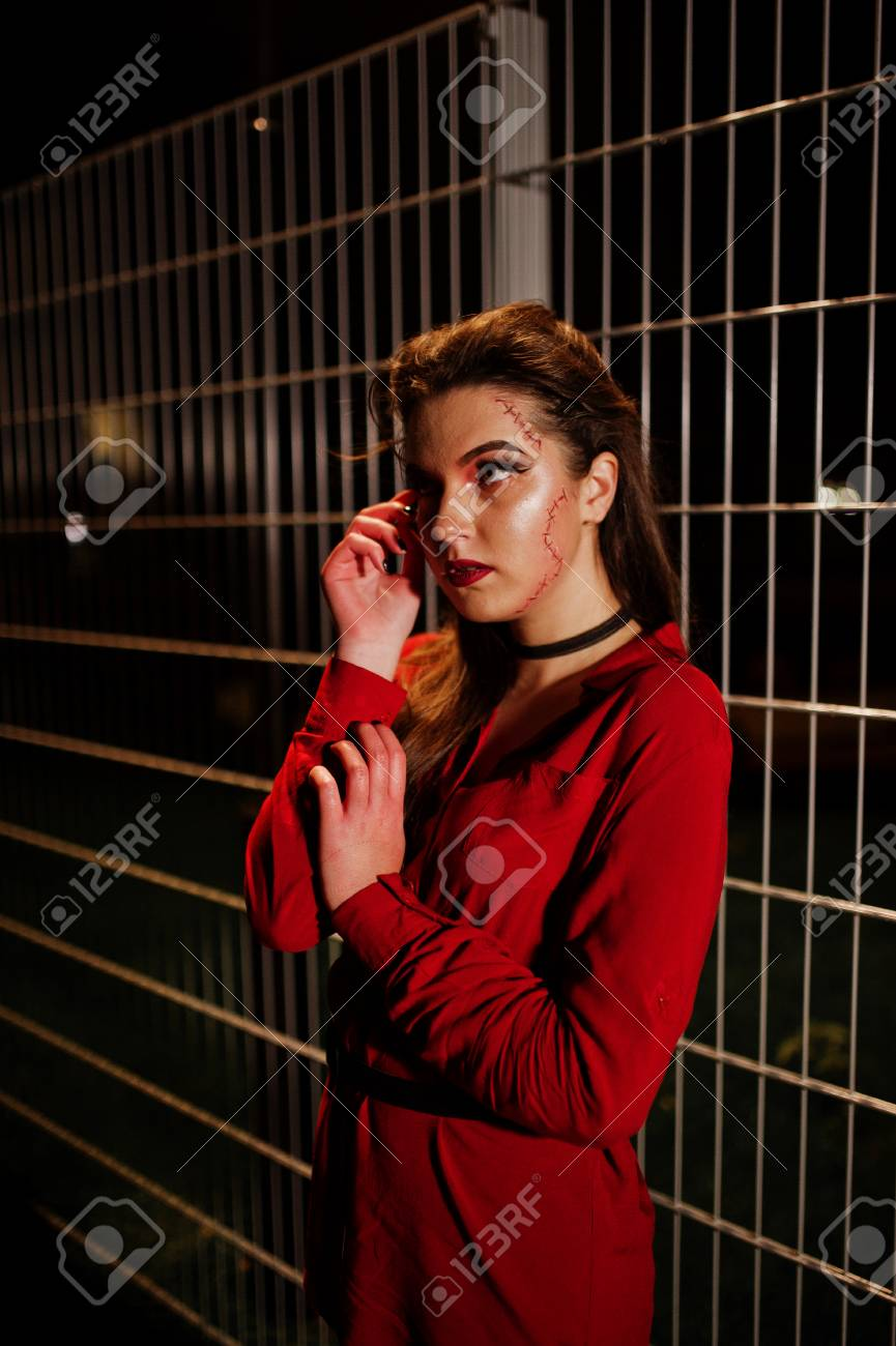 1a3aa5a7 Black girl in red shirt and bright make-up on night street outdoor against  cage