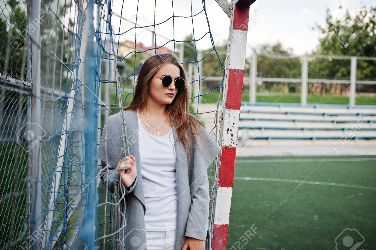 low priced 161bc d94e2 Girl in gray coat with sunglasses at small street stadium football..