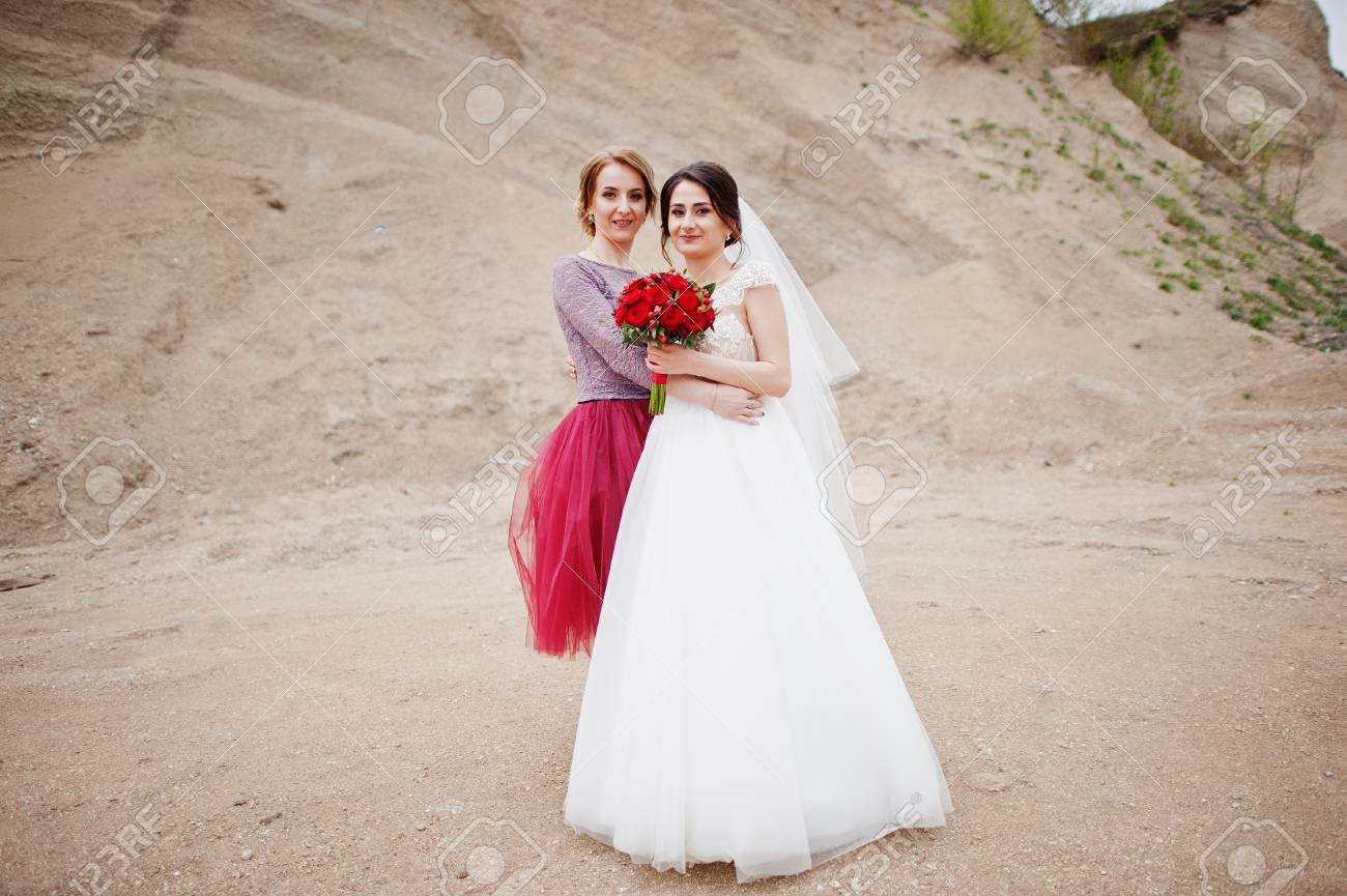 Bride Posing With Her Bridesmaid In Sand Quarry On Her Wedding