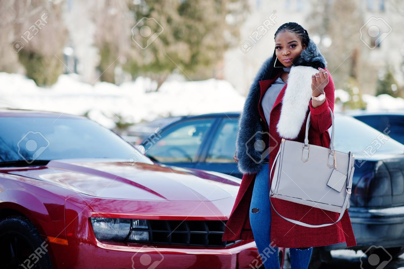 Rich african american girl in red coat and fur against red muscle