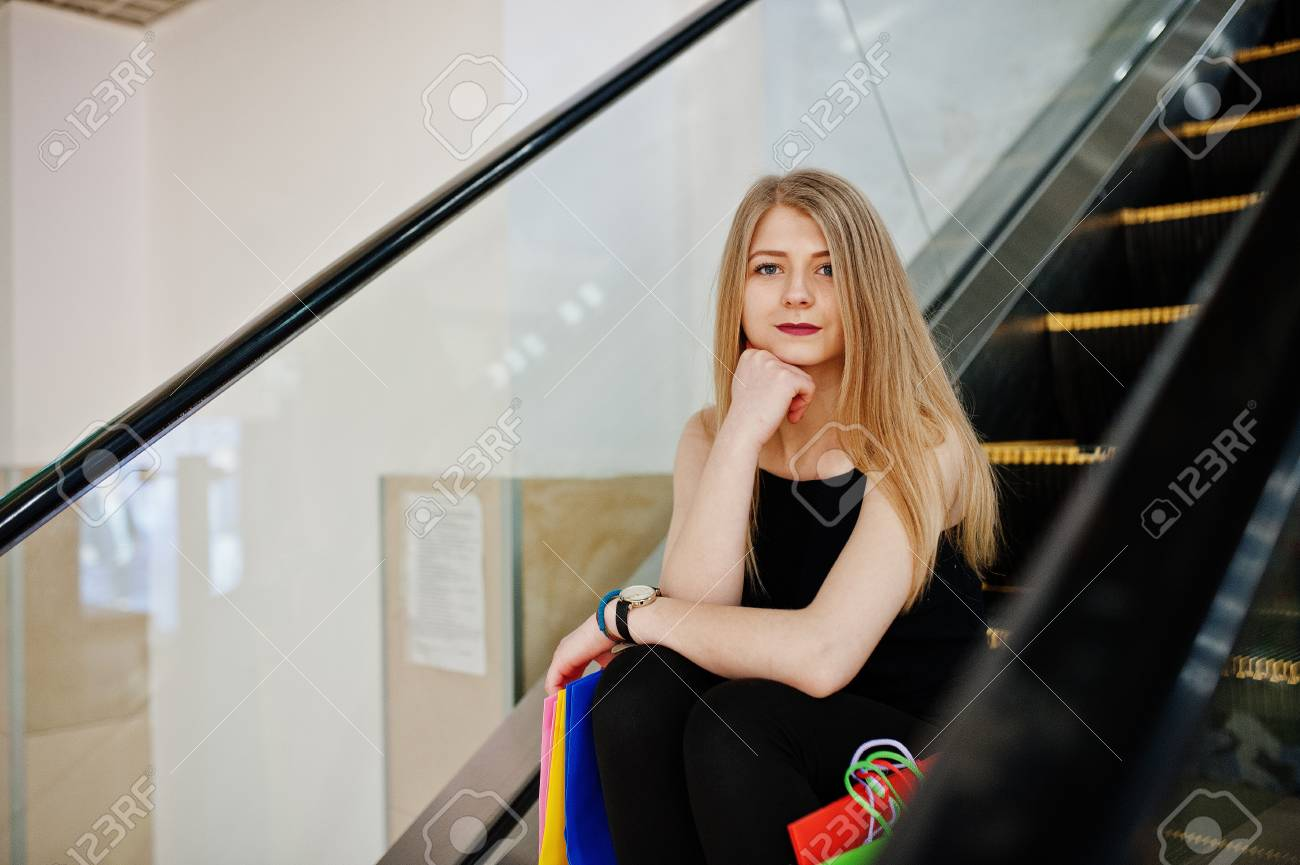 Girl with shopping bags in the mall at the escalator